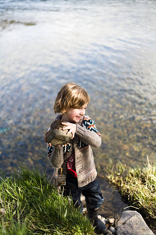 young boy playing on the river. by Darren Muir for Stocksy United
