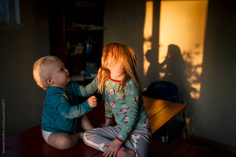 Baby boy pulls his big sister's hair in golden light by Amanda Voelker for Stocksy United