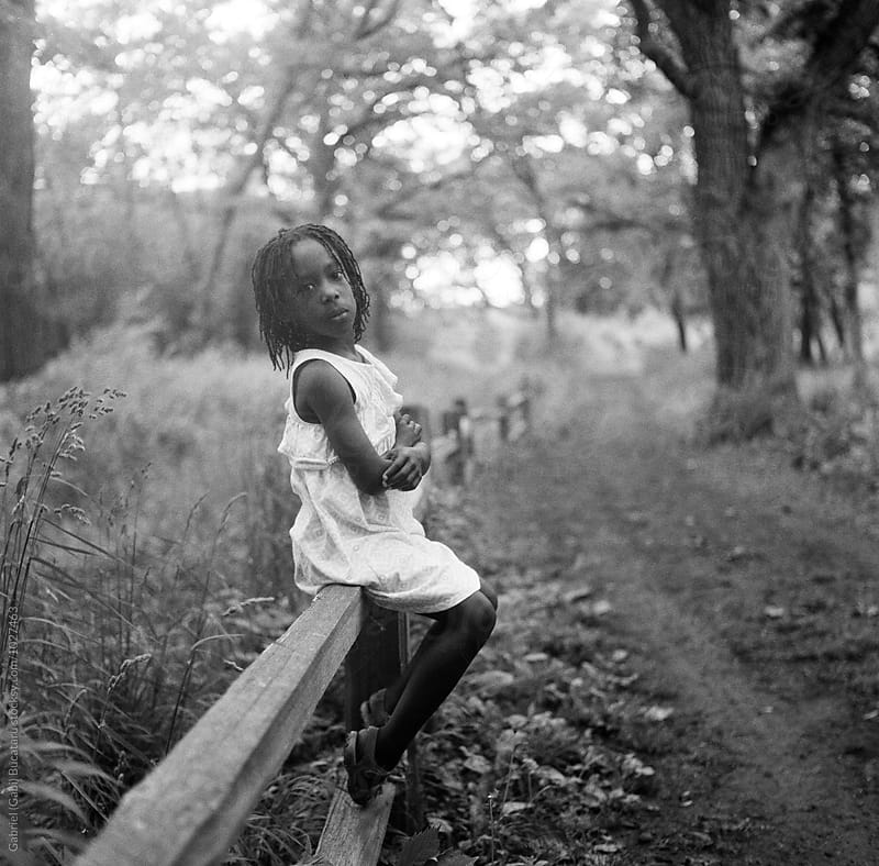 African American girl sitting on a fence in a forest by Gabriel (Gabi) Bucataru for Stocksy United