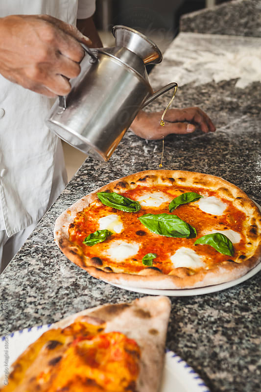 Pouring Olive Oil on Baked Margherita Pizza by Giorgio Magini for Stocksy United