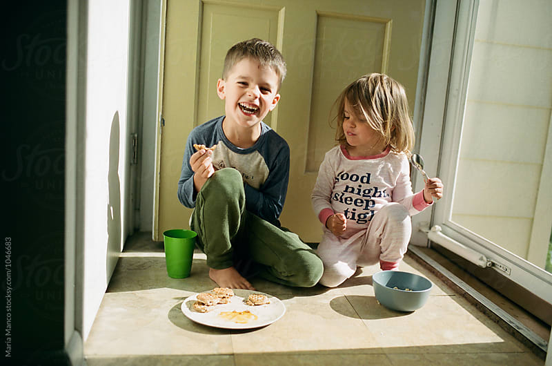 children eating breakfast by door by Maria Manco for Stocksy United