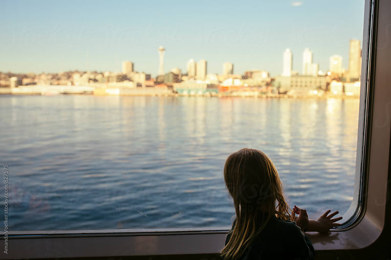 Little Girl Looks at the Skyline Through the Ferry Window by Amanda Voelker for Stocksy United