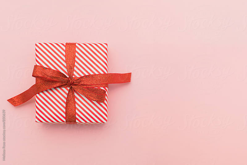Small red and white wrapped gift on pink - wide by Melissa Ross for Stocksy United