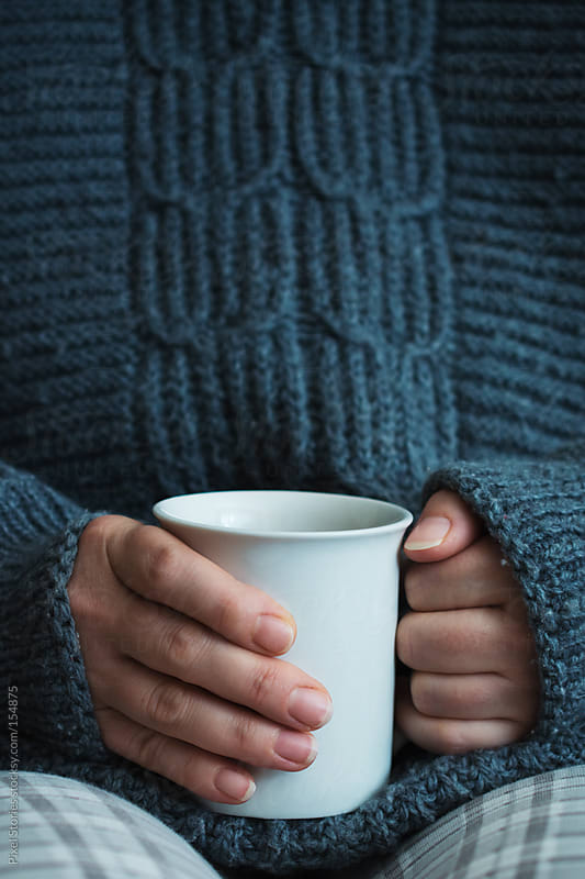 Woman holding hot drink by Pixel Stories for Stocksy United