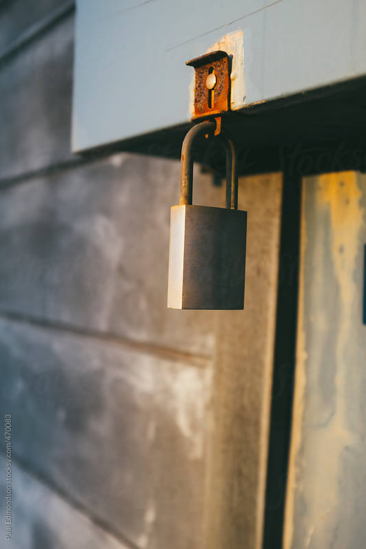 Old padlock on building exterior, close up by Paul Edmondson for Stocksy United