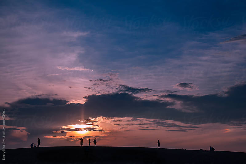 Silhouetted people on hill as sunsets by Kerry Murphy for Stocksy United