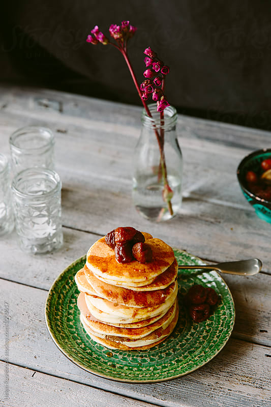 Pancakes made with Ricotta and served with baby figs in rum syrup. by Helen Rushbrook for Stocksy United