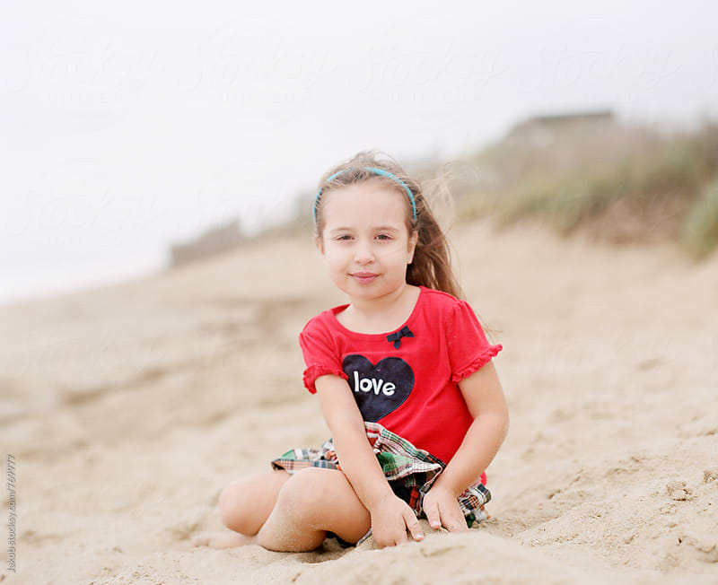 Cute young girl sitting on a beach in windy weather by Jakob for Stocksy United