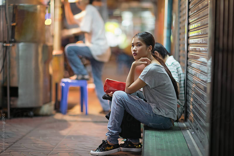 Young Asian Woman Sitting on the Street by Lumina for Stocksy United
