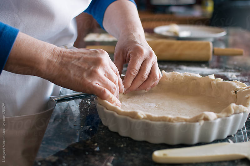 woman crimps edge of pie crust by Margaret Vincent for Stocksy United