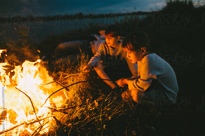 Boys lighting their sticks with the night fire  by Evgenij Yulkin for Stocksy United