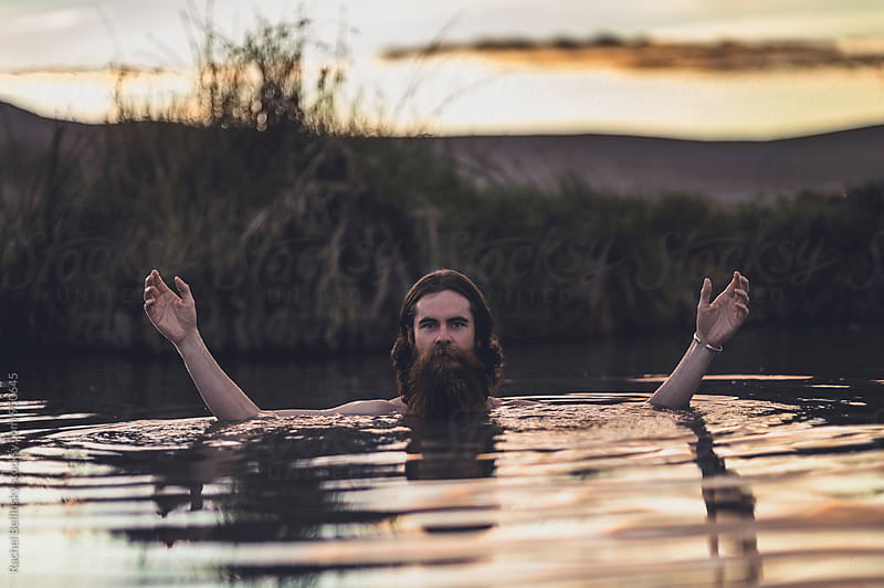 A bearded man resembling Jesus submerged in water at sunset by Rachel Bellinsky for Stocksy United