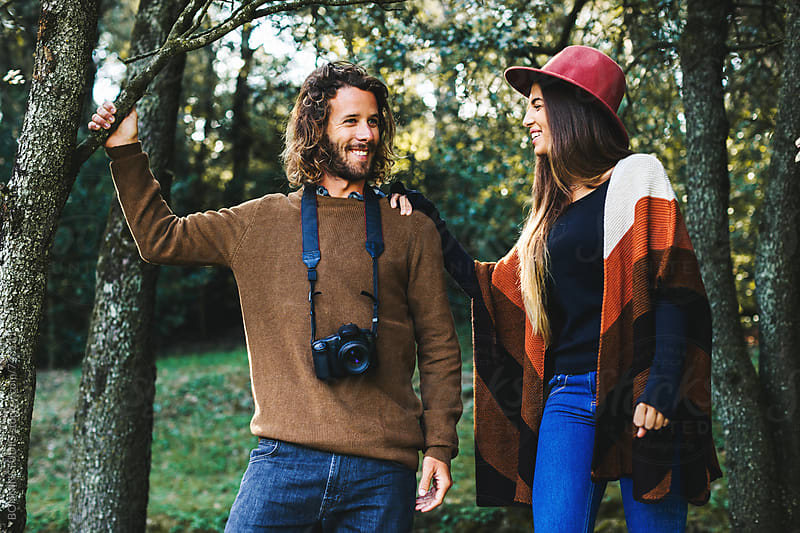 Hipster couple standing in the woods. by BONNINSTUDIO for Stocksy United