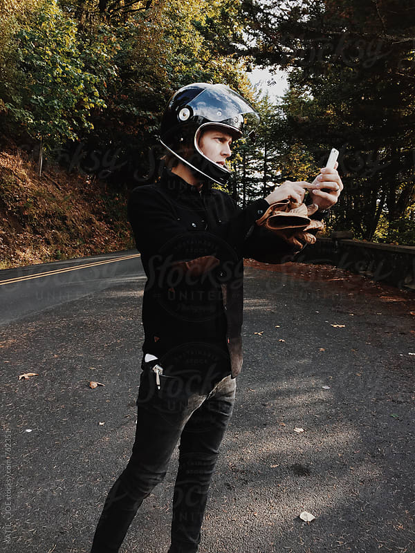 Man wearing a motorcycle helmet taking a picture with his phone by KATIE + JOE for Stocksy United