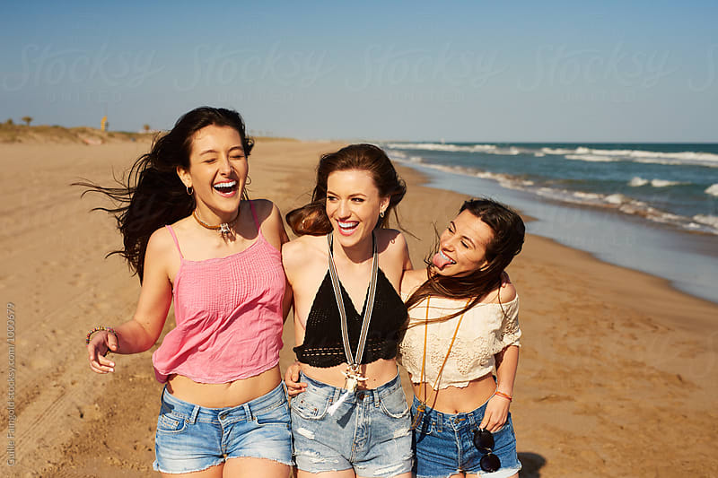 Three cheerful girl walking on beach by Guille Faingold for Stocksy United