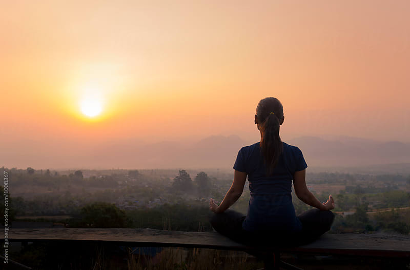 Woman meditating with view of rising sun over the mountains by Søren Egeberg Photography for Stocksy United