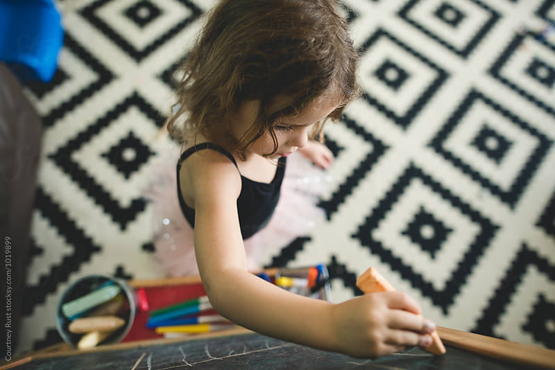 Bird's eye view of girl drawing with chalk  by Courtney Rust for Stocksy United