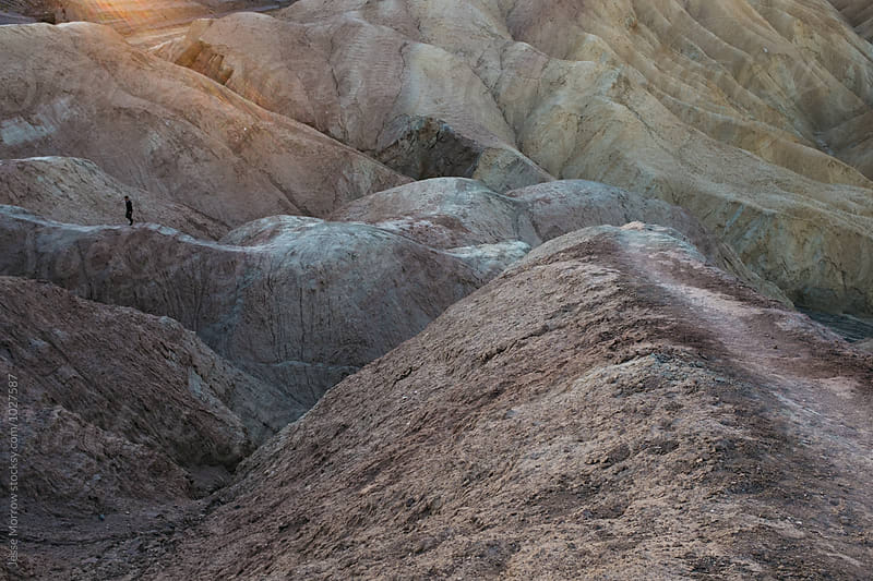 person walks across hills at zabriski point death valley national park  by Jesse Morrow for Stocksy United