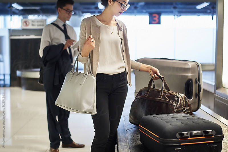 Young woman picks up her traveling bag at luggage return belt