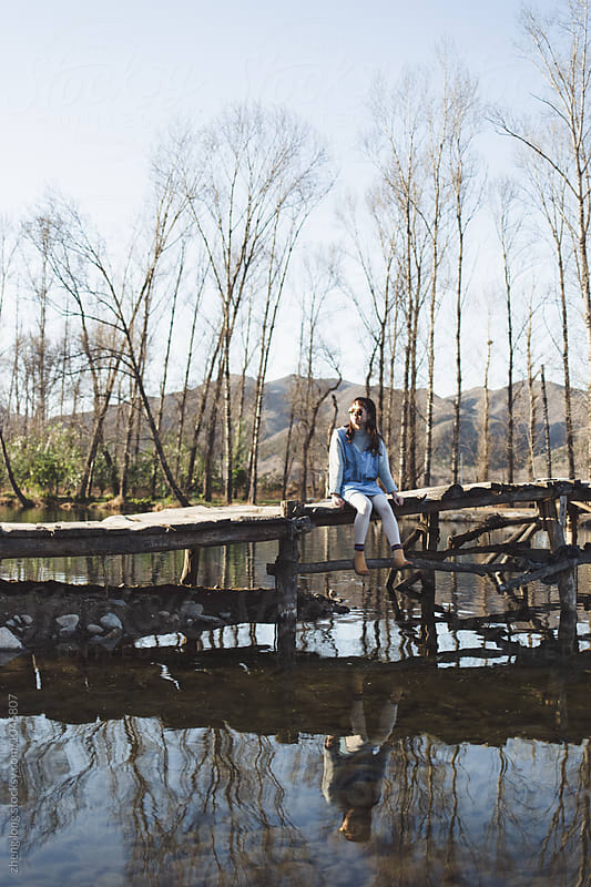 young girl sitting on the wooden bridge  by zheng long for Stocksy United