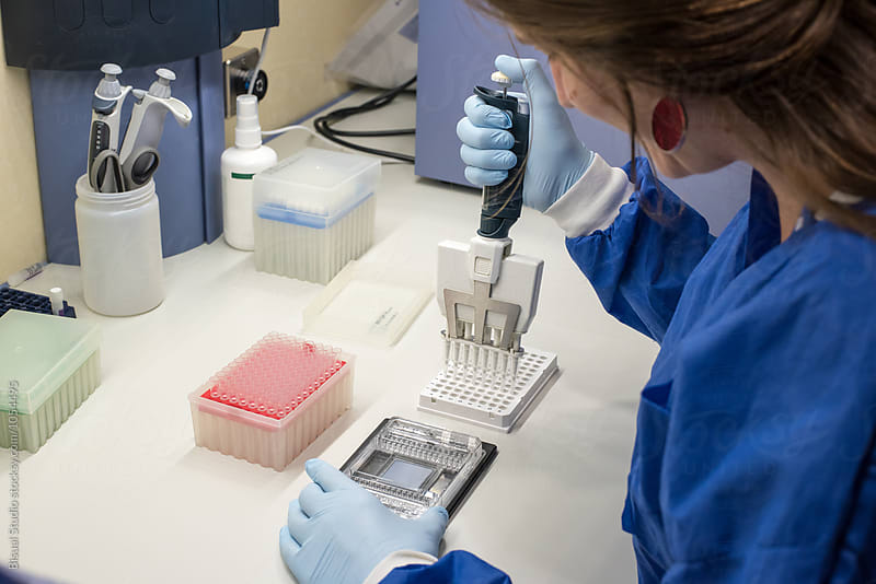 Female scientist on a laboratory working with a multi-pipette and a DNA chip by Bisual Studio for Stocksy United