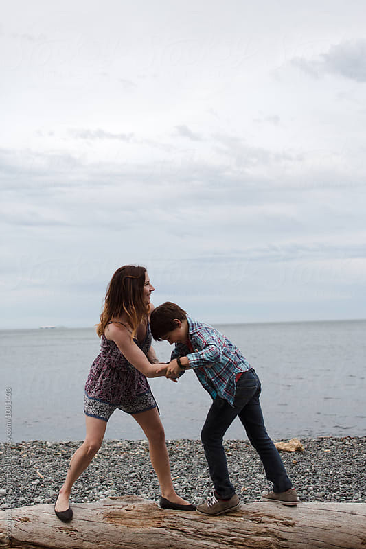 Mom and son spending time together outside in nature wrestling by Rob and Julia Campbell for Stocksy United