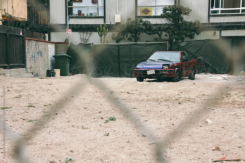 Old vintage car on sand parking seen through a fence by Alejandro Moreno de Carlos for Stocksy United