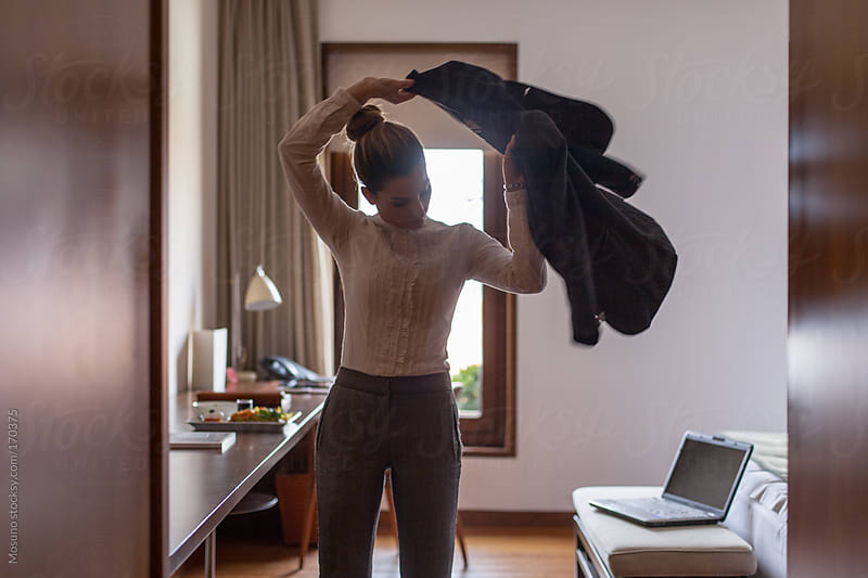 Woman Putting Her Jacket on in a Hotel Room by Mosuno for Stocksy United