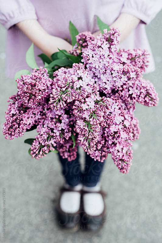 Young girl holding a bouquet of lilac by Emoke Szabo for Stocksy United
