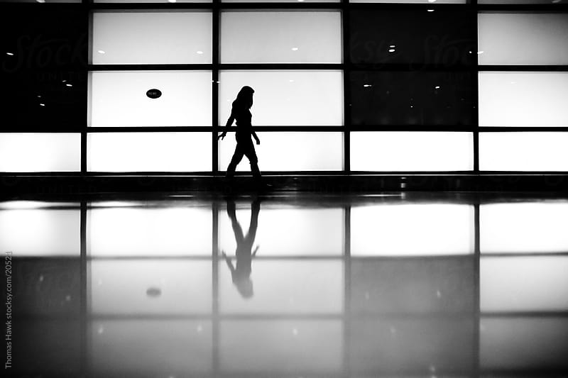 Woman walking at airport by Thomas Hawk for Stocksy United