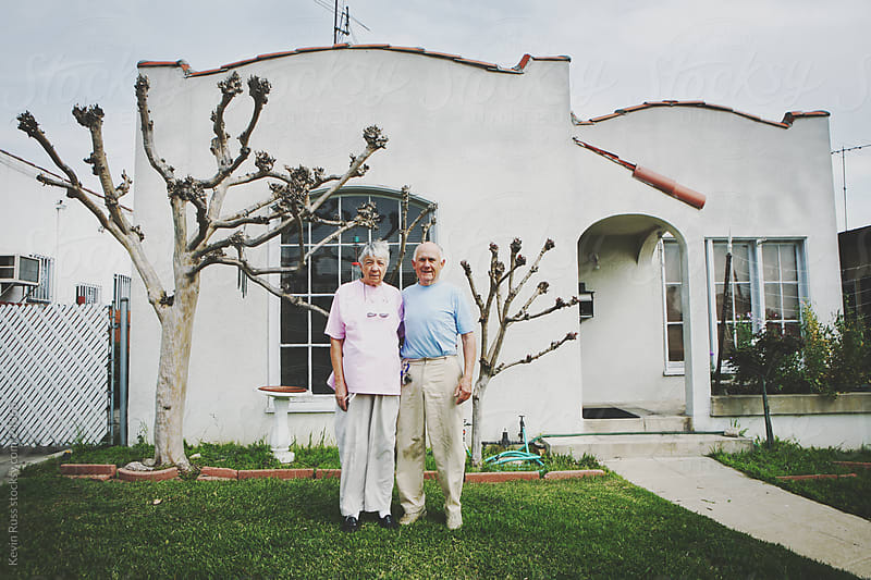 Elderly Couple in Front of Home by Kevin Russ for Stocksy United