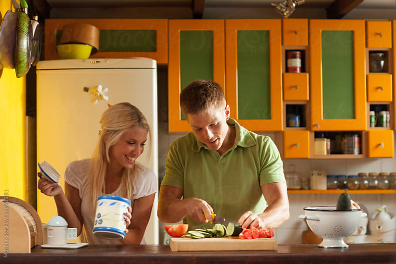 Happy couple cooking lunch at home. by Mosuno for Stocksy United