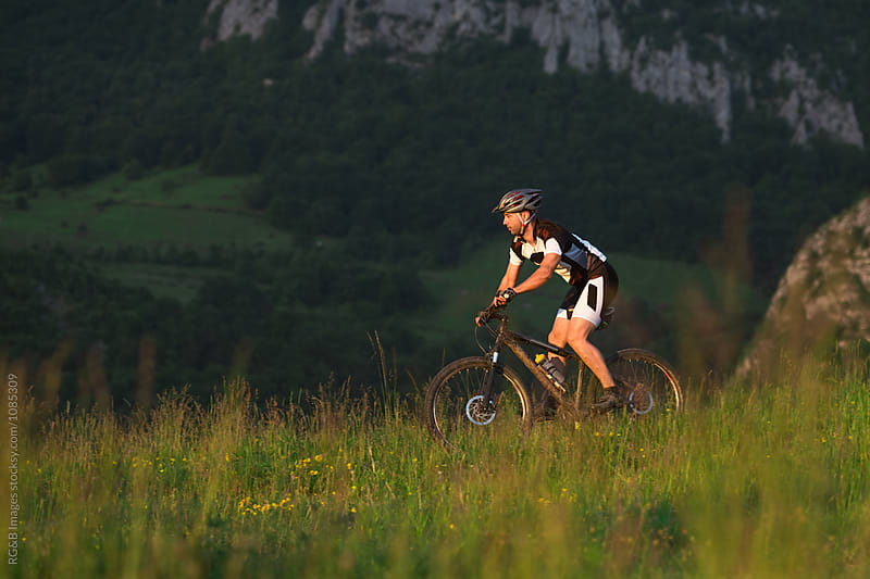 Man on bycicle crossing a meadow near the mountain by RG&B Images for Stocksy United