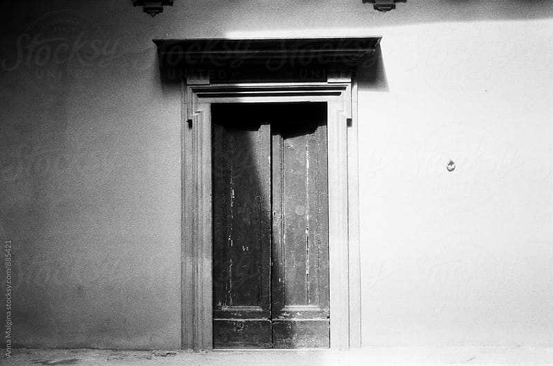 A black and white film photo of old italian door  by Anna Malgina for Stocksy United