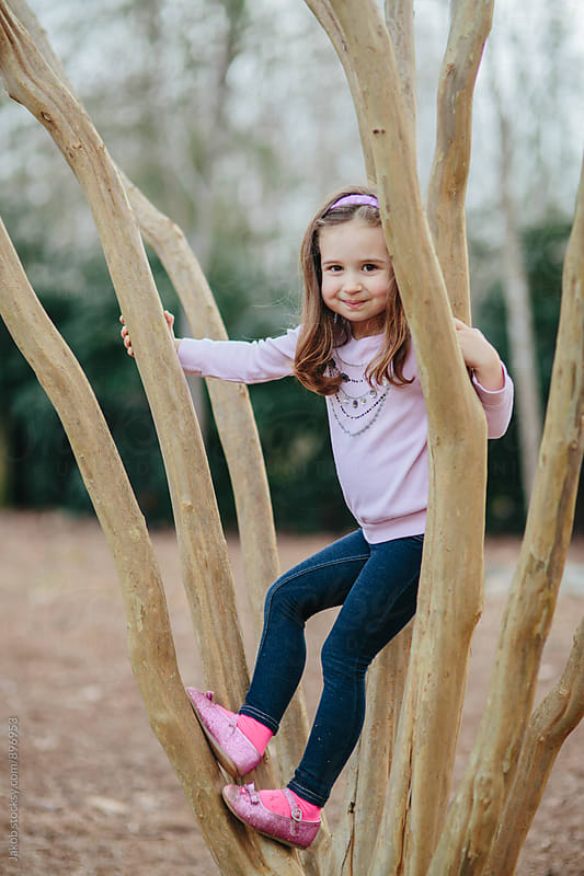 Cute young girl climbing a tree outside by Jakob for Stocksy United