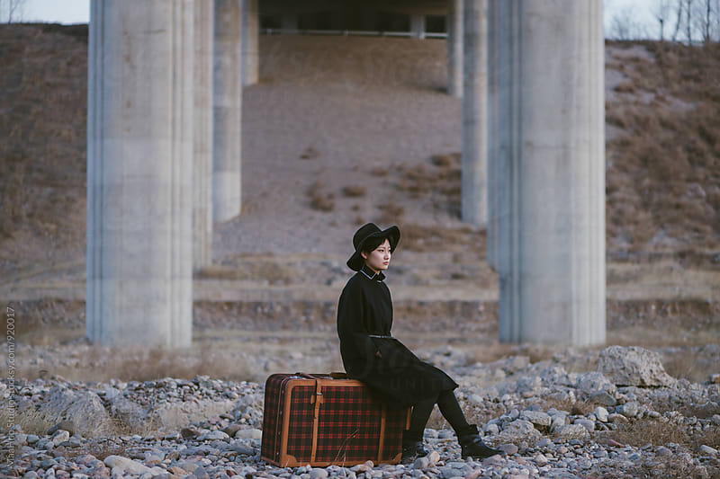 Young chinese woman sitting on a classic suitcase by Maa Hoo for Stocksy United