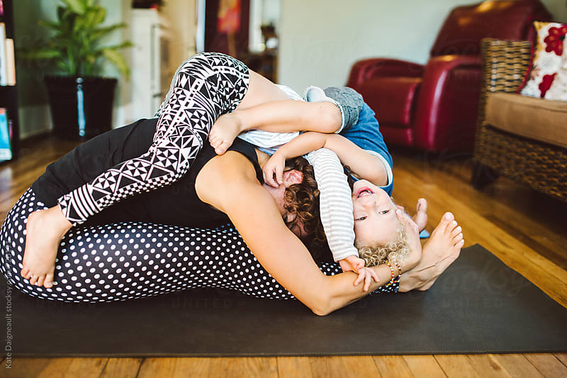 Young family doing yoga together. by Kate Daigneault for Stocksy United
