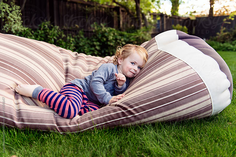 Toddler with cheeky smile lying on a beanbag in a yard in the evening by Angela Lumsden for Stocksy United