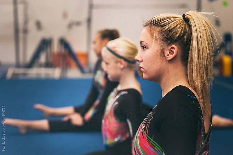 Gymnastics: Row Of Teens Doing Split During Stretching by Sean Locke for Stocksy United