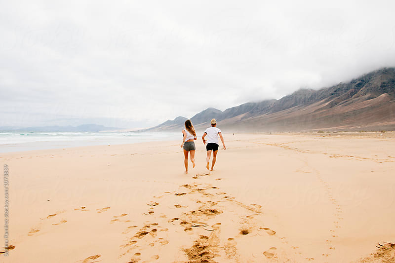 Young couple running along the beach by Susana Ramírez for Stocksy United