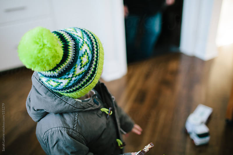 a little boy in a knit hat with pompom indoors on his way out by Sarah Lalone for Stocksy United