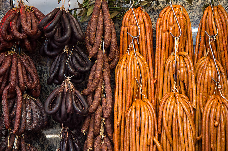 Hanging raw sausages at the market by Bisual Studio for Stocksy United