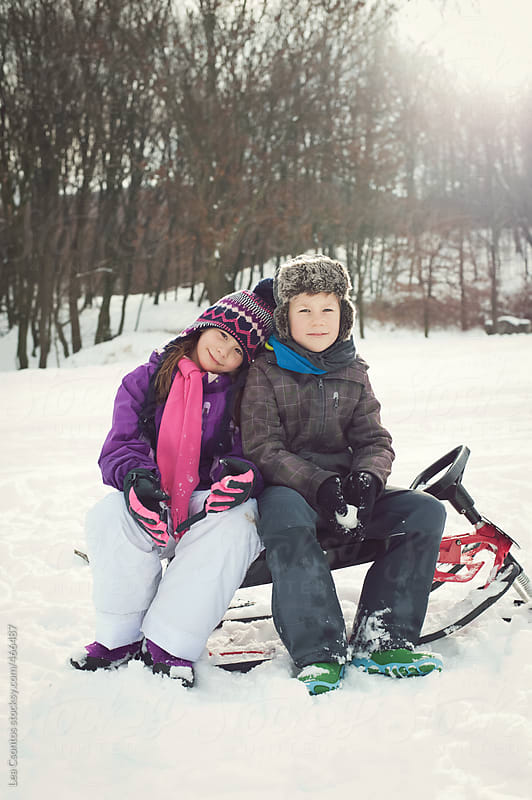A young girl and a boy sitting on a sledge having some rest with snow around by Lea Csontos for Stocksy United