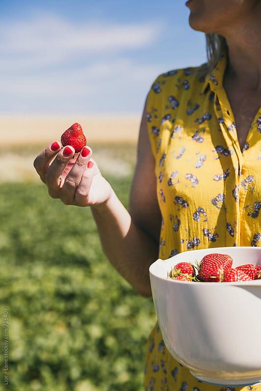 Woman holding freshly picked strawberry by Lior + Lone for Stocksy United