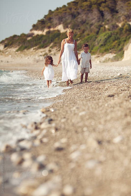 Family walking on the beach by Dejan Ristovski for Stocksy United