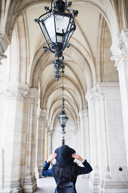 Back view of a young woman standing in a city hall by Jovana Rikalo for Stocksy United