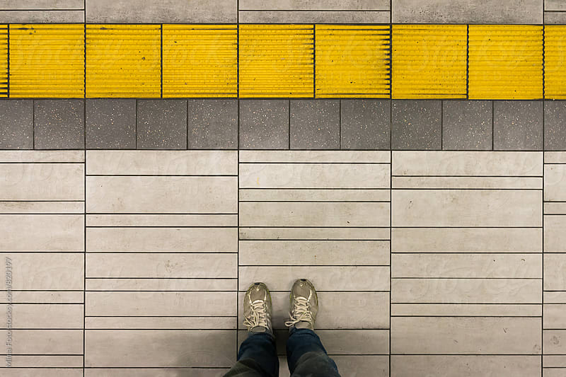 Standing on subway platform with yellow stripe by Mima Foto for Stocksy United