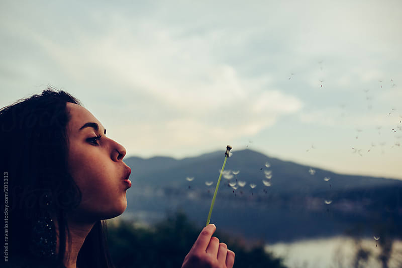 Girl blowing dandelion  by michela ravasio for Stocksy United