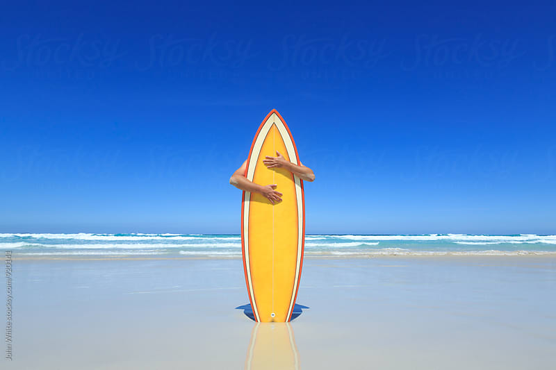Hugging a surfboard. by John White for Stocksy United