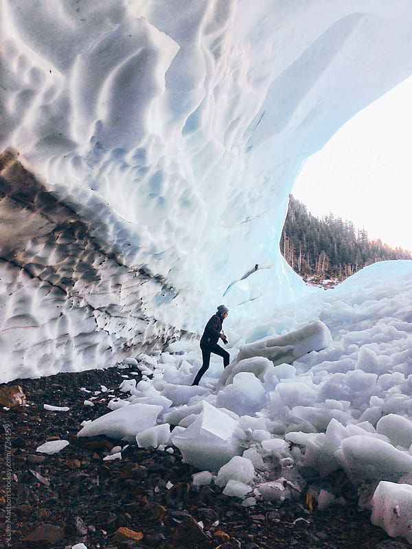 A Man Walks Out Of A Towering Ice Cave While Clutching His Camera by Luke Mattson for Stocksy United